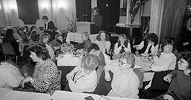 Sigrún Sigurðardóttir að kynna hugmyndafræðigrundvöll framboðsins. Aftara borð, Helga Thorberg, Hjördís Hjartardóttir, Ingibjörg Sólrún Gísladóttir, Kristín Jónsdóttir, Þórhildur Þorleifsdóttir, Kristín Ástgeirsdóttir. Fremra borð, Helga Jóhannsdóttir, óþekkt, Guðrún Ólafsdóttir og Magdalena Schram.